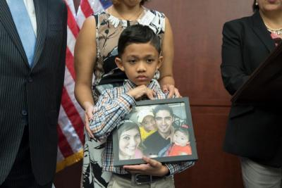 Seven-year-old Walter Escobar of Texas holds a photo of his family, including his father, Jose Escobar, who was deported from the U.S., during a late March news conference on Capitol Hill in Washington. Experts say law-abiding migrants are at greater risk of deportation under President Donald Trump.