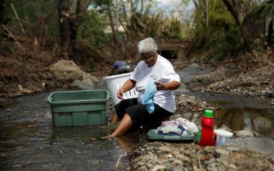 Sara Ocasio, who was affected by Hurricane Maria, washes clothes in a river Oct. 9 near her home in the Trujillo Alto municipality outside San Juan, Puerto Rico. Nearly three weeks after Hurricane Maria tore through the Caribbean, Puerto Rico remains with little clean water, little electric power and almost no telecommunications.