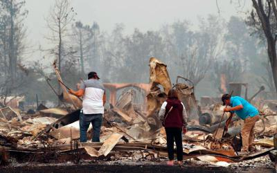 Residents look through the remains of their destroyed home Oct. 9 after wildfires in Santa Rosa, Calif. A series of deadly Northern California wildfires has killed at least 17 people, destroyed more than 2,000 buildings, including a section of Cardinal Newman High School in Santa Rosa.