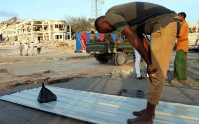 """A volunteer prays Oct. 17 at the scene of an explosion in Mogadishu, Somalia. Before concluding his weekly general audience Oct. 18, Pope Francis expressed his sorrow and denounced the Oct. 14 """"massacre, which caused more than 300 deaths, including several children."""""""