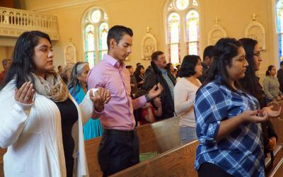Young Hispanics, including Mirna Lozano, Carlos Guzman and Dora Lozano, front right, recite the Lord's Prayer during a young adult Mass in late October at St. Dominic Church in Springfield, Ky. The three young people are among 800,000 young people nationwide currently protected by the Deferred Action for Childhood Arrivals program, or DACA. (CNS photo by Ruby Thomas/The Record)