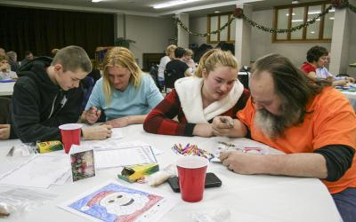 <p>Christian Inman (left) plays a game with his mother, Tracy Inman, while his sister, Katelyn, colors with their father, Jimmy Inman, at the CrossOver Prison Ministries' Holiday Party at First Christian Church in Omaha, Neb., Dec. 5. </p>