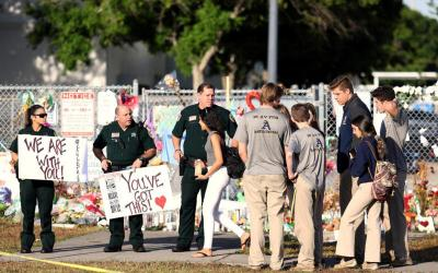 """Police and law enforcement officers show their support as students arrive Feb. 28 at Marjory Stoneman Douglas High School in Parkland, Fla., for the first time since the Feb. 14 mass shooting. The chairmen of the U.S. bishops' committees on domestic policy and Catholic education issued a joint statement March 5 calling on the nation's leaders to come up with """"common-sense gun measures."""" (CNS photo by Mary Beth Koeth, Reuters)"""