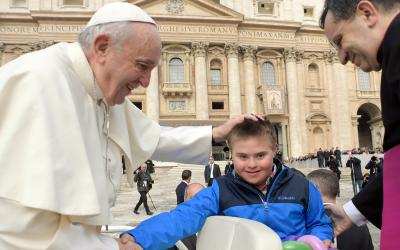 Pope Francis greets Peter Lombardi, 12, of Columbus, Ohio, after the boy rode in the popemobile during his general audience in St. Peter's Square at the Vatican March 28. Receiving a kiss from the pope was a wish come true for Peter, who has Down syndrome and has survived leukemia. (CNS photo by Vatican Media)