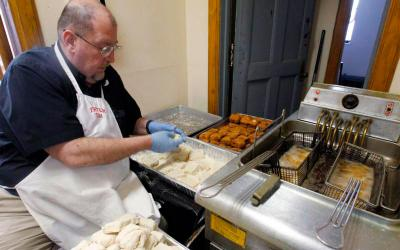 Msgr. Tim Stein, pastor of St. Mary's Parish in Altoona, Pa., checks the temperature of fish during a 2013 fish fry at the parish hall. He died at the parish rectory April 20 at age 60. (CNS photo by Bob Roller)