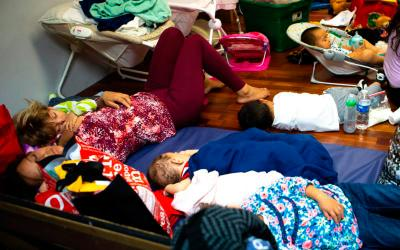 Exhausted immigrants, recently released from U.S. custody, sleep on the floor of a Catholic Charities-run respite center in McAllen, Texas, July 1, as several U.S. bishops tour the facility. A delegation of U.S. bishops has traveled to the Diocese of Brownsville, Texas, to learn more about the detention of Central American immigrants at the U.S.-Mexican border. (CNS photo by Chaz Muth)