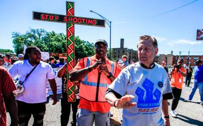"""Father Michael Pfleger, pastor of St. Sabina Parish in Chicago, leads the """"Dan Ryan Shut Down"""" protest July 7 in Chicago. Father Pfleger and hundreds of anti-gun activists filled a major Chicago highway for about an hour demanding that city officials do something to stop gun violence in the city. (CNS photo by Tannen Maury/EPA)"""