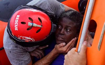 A crew member of the Spanish nongovernmental organization Proactiva Open Arms comforts a rescued African migrant July 17 in central Mediterranean Sea. The main mission of the NGO is sea rescues of refugees that arrive in Europe fleeing wars, persecution or poverty. (CNS photo by Juan Medina/Reuters)