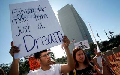 "A protester holds a sign that reads ""Fighting for more than just a Dream,"" as he joined Dreamers and hundreds of demonstrators calling for Deferred Action for Childhood Arrivals, or DACA, in early February outside the Federal Building in Los Angeles. A federal judge in Washington has ordered the Trump administration to restore DACA, saying reasons for ending it are not justified. (CNS photo by Mike Nelson/EPA)"
