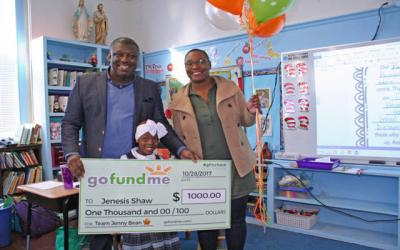 <p>Nazareth Elementary School student Jenesis Shaw and her parents, Micheal and Scotesha, pose with a $1,000 check Jenesis received Nov. 28 from Go Fund Me for her efforts to raise money for children with cancer.  </p>