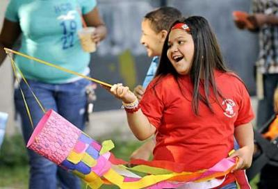 Third-grader Nayeliz Ocasio takes part in a moving-on day parade at Henry Hudson School No. 28 in Rochester June 18. The school offers bilingual classes at each grade level.