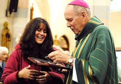 Liz Flanagan shares some photographs with Bishop Matthew H. Clark after a young-adult Mass Feb. 6 at Rochester's Blessed Sacrament Church.