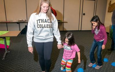 <p>Ithaca College student Julia Sideri of Long Island helps Caroline Vajk during the Play 'n Talk program at the Tompkins County Public Library in Ithaca Dec. 3.  </p>