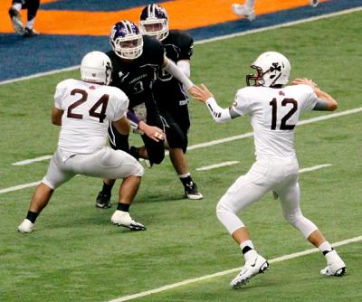 Aquinas quarterback Jake Zembiec looks to pass during the state-championship game at the Carrier Dome in Syracuse Dec. 1. Zembiec earned game Most Valuable Player honors by throwing for 211 yards and three touchdowns.