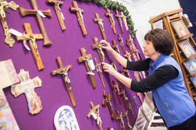<p>Mary Young restocks items at the Divine Mercy Shop in Spencerport. The store is located in the former St. John the Evangelist School.  </p>