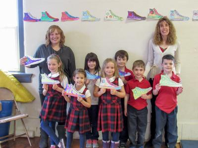 Principal Ms. Elizabeth Jensen and First Grade teacher Mrs. Audrey Walck with 1st grade students as they show off 'sneakers' earned doing chores and good deeds. Students purchased a sneaker for $3 (one foot in quarters) with the money collected being donated to the Multiple Sclerosis Association. Front Row: Lydia Kashorek, Kate Schwan, Malea Benson, Andrew Schlueter and Henry Davis. Back Row students:  Ava Bellanca and Padraic Flaherty.