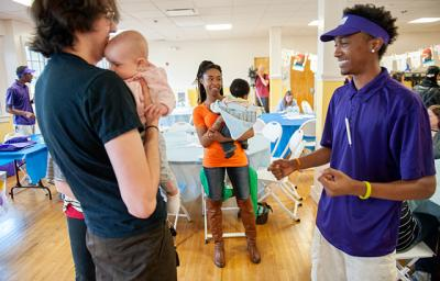 Derrell Jackson (right) shows some baby-and-me exercises to Alexander Bullinger (left) and his 4-month-old daughter Hailey and Unique Balkum (center) and her 5-month-old son Chancellor.