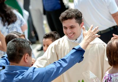 Deacon Juan Benitez in congratulated by friends after the May 28 ordination Mass at Rochester's Sacred Heart Cathedral.