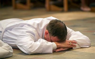 <p>Deacon James Fien prostrates himself before the altar during the 2017 deacon ordination Mass at Rochester's Sacred Heart Cathedral. (File photo) </p>