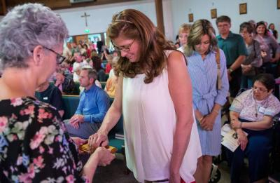 <p>During a Lourdes Virtual Pilgrimage Experience May 8 at Auburn's Sacred Heart Church, Sharon Nelson places her hand on a rock from the grotto where Mary reportedly appeared to St. Bernadette Soubirous.  </p>