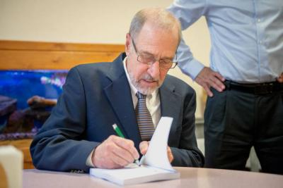 <p>Local author John Strazzabosco signs a copy of his new book, <em>Ninety Feet Under: What Poverty Does to </em><em>People</em>, at Mercy Center in Brighton June 14. (Courier by John Haeger)  </p>