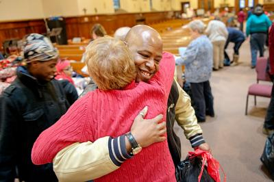 Junebug Brown hugs volunteer Becky Orsini after Orsini helped him wrap presents for his family Dec. 17 during the Christmas Blessing Project, an annual giveaway at Rochester's Holy Apostles Church.
