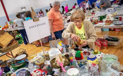 <p>Josie Locke, a longtime Peace of Christ parishioner, works to straighten up a table of items for sale July 12 during the annual parish garage sale held at St. Ambrose Academy in Rochester. Locke turned 100 in March. (Courier photo by John Haeger)  </p>