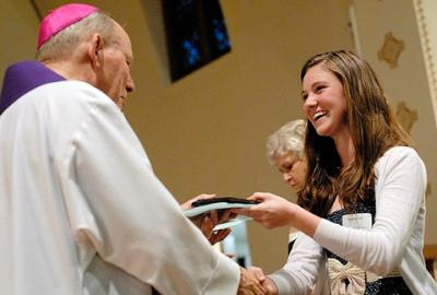 Michelle Hart, a parishioner of St. Catherine of Siena Church in Mendon, receives her Hands of Christ plaque from Bishop Matthew H. Clark during a March 21 recognition ceremony for high-school seniors at Victor's St. Patrick Church.