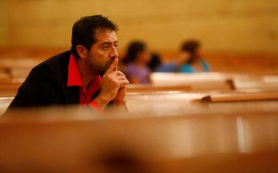 <p>Ernesto Vega listens during a Nov. 10, 2016, prayer service at the Cathedral of Our Lady of the Angels in Los Angeles. Duke University's Center for Spirituality, Theology and Health reported in 2015 that an analysis of more than 1,500 reputable medical studies indicates people who are more religious and pray more have better mental and physical health. (CNS photo by Patrick T. Fallon/Reuters)  </p>