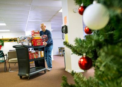 Bob Capellazzi pushes a cart of food items to be distributed through the food pantry at St. Jude the Apostle church in Gates Dec. 21.