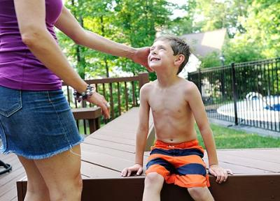 Five-year-old Nathan VanDeVoorde, who has suffered three bouts of meningitis, looks up at his mother, Julie, by the pool at their home June 21.