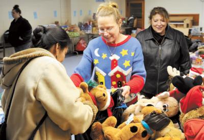 Catholic Charities of Livingston County volunteer Tina Ashley (center) helps Elizabeth Medina (left) and Gena Thomspon pick out children's toys in Mount Morris Dec. 12, 2013, as part of the agency's Christmas giving program.