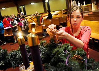 Charlotte Nazarian, 11, lights an Advent candle in December 2011 at Fairport's Church of the Assumption.