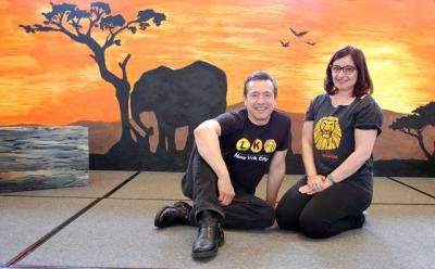 "Enrique Segura, a Broadway actor, and his wife, Kristi, a choreographer, pose on the set of ""The Lion King Jr."" in early May at the School of Sacred Heart St. Francis de Sales in Bennington, Vt. ""The Lion King Jr.,"" a 60-minute adaptation of the show about love and redemption, was created especially for the strengths and skill level of middle- school students."