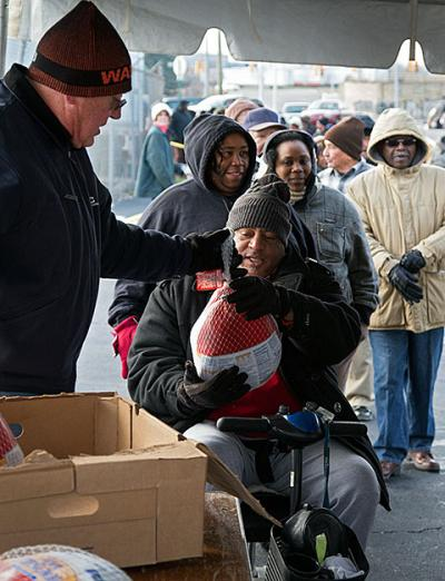 People in need line up for free Thanksgiving turkeys last year in Detroit.  The 50th anniversary of President Lyndon Johnson's declaration of the War on Poverty Jan. 8 prompted a renewed commitment by Catholic and other faith groups to address poverty.