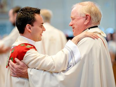 Father Carlos Sanchez (left) is congratulated by Father James Schwartz during the 2015 priest ordination.