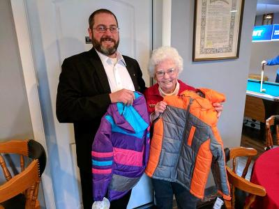 Council #243 Grand Knight Gary Mikolajczyk presents Sr. Susan Cain with the coats.