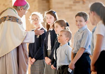 Bishop Salvatore R. Matano celebrated a Mass with students at St. Joseph School in Penfield Jan. 28. Above, Bishop Matano talks to first-grader Cole Reazor (bottom center) during his homily.