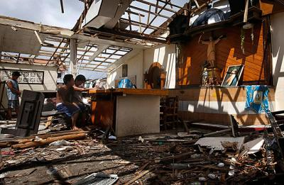 Residents pray inside a chapel damaged by Typhoon Haiyan in Tanauan, Philippines, Nov. 14. The central province of Leyte took the brunt of the powerful storm that left hundreds of thousands of people without shelter.