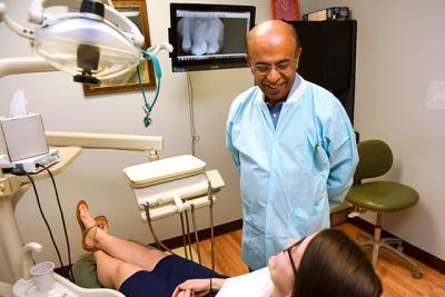 Dr. Jay Mruthyunjaya, a dentist from Brighton, volunteers at St. Joseph's Neighborhood Center in Rochester Aug. 18.