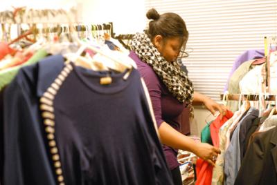 Samantha Colson, a staff member at Catholic Family Center, sorts clothes in the clothing room.