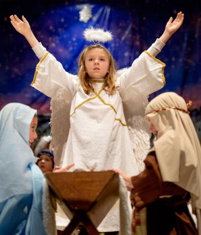 """The Nativity angel, played by second-grader Sarah Glazier, visits Mary and Joseph at the end of """"The Living Creche,"""" a Christmas production presented by students at St. Rita School in Webster, Dec. 11, 2014."""