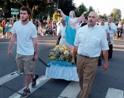 <p>Noah Bastedo and Dave VanHanchan carry a statue of Mary on a bier at the beginning of the Clyde Fire Department's parade Aug. 12.  </p>