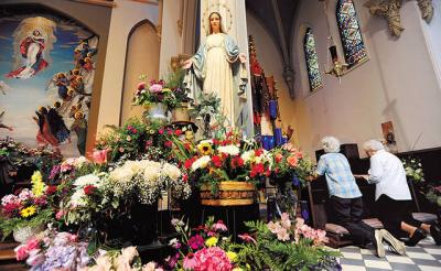<p>Two women pray near a statue of Mary surrounded by flowers Aug. 14. 2009 during the annual Flower Festival at Auburn's St. Mary Church.  </p>