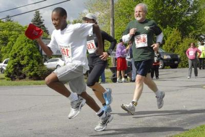 Eleven-year-old Cory Ruddock (from left), Caroline Coyle and John Welc head for the finish line of the 14th-annual Run For the Young 5K May 8 at Greece's St. Lawrence Church.
