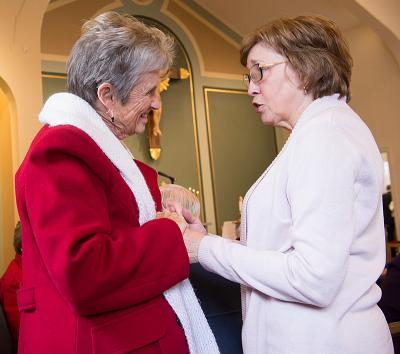Sister Jackie Glessner of Connecticut talks with Evelyn McLaughlin Sabino before a Feb. 26 Mass at Rochester's Church of the Annunciation. The liturgy marked the 50th anniversary of the 1967 fire at St. Philip Neri Church that claimed the lives of Father George Weinmann and Sister Lilian Marie McLaughlin, SSND. Sister McLaughlin was Sabino's sister and Sister Glessner's classmate.