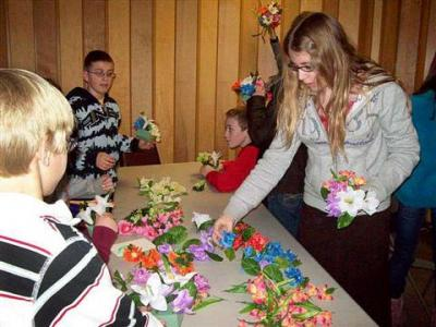 Children prepare flowers and a tomb for a Living Stations of the Cross performance that was held March 26 at St. Francis Church in Phelps.