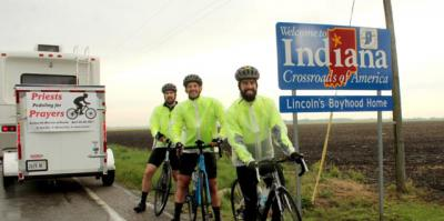 "After riding a little more than 340 miles over five days, Father Michael Pica, Father Adam Cesarek and Father Tom Otto stand just inside Indiana April 28, bringing ""Priests Pedaling for Prayers"" to a close. Behind them is one of the support vehicles that accompanied them on the journey to raise prayers for and awareness of vocations."