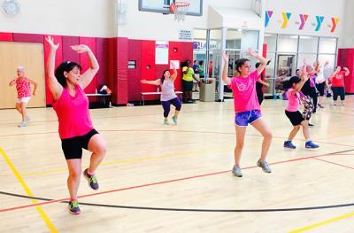 "Jennifer Gaudino (left) and her daughter, Cecilia Hoskins, take part in a zumba class that was offered Aug. 10 as part of the Rochester Latino Rotary Club's ""Dance to Health"" at the Maplewood YMCA in Rochester."