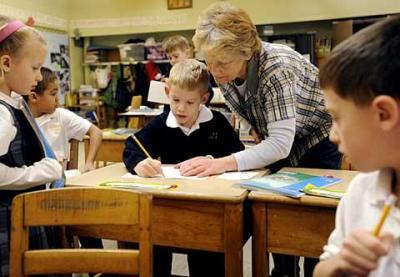 St. Mary Our Mother School in Horseheads celebrated its 50th anniversary this past September. Above, first-grade teacher Karen White helps Tyler Stickler with writing assignment.